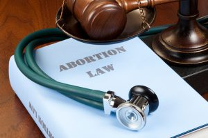 """Concept shot. Gavel, stethoscope and scale of justice next to Abortion Law book."""