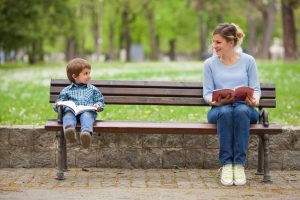 Young woman and cute little boy reading books in a park and talking